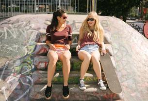 Two female skateboarding friends chatting in skateparkの写真素材 [FYI03558940]