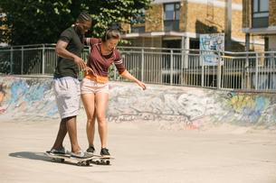 Young man and woman practising skateboarding balance in skateparkの写真素材 [FYI03558949]