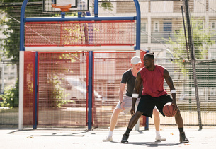 Two male basketball players practising on basketball courtの写真素材 [FYI03558960]