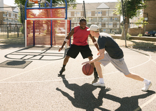 Two male basketball players practising on basketball courtの写真素材 [FYI03558961]