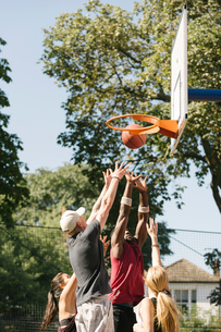 Female and male basketball players throwing ball at basketball hoopの写真素材 [FYI03558968]