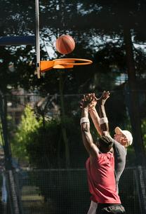 Young male basketball players throwing ball at basketball hoopの写真素材 [FYI03558971]
