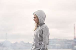 Female runner in grey hoody on misty docksideの写真素材 [FYI03559031]