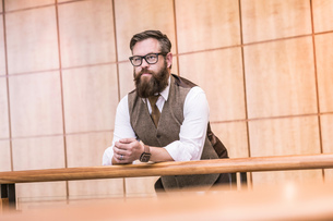 Businessman wearing tweed waistcoat looking out from  office balconyの写真素材 [FYI03559054]