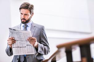 Businessman reading newspaper on office balconyの写真素材 [FYI03559059]