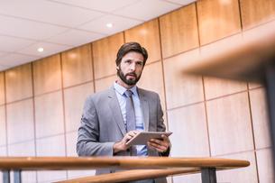 Businessman using digital tablet touchscreen on office balconyの写真素材 [FYI03559065]