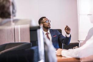 Window view of businessman questioning in board meetingの写真素材 [FYI03559080]