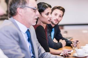 Businesswoman and businessmen listening in board meetingの写真素材 [FYI03559082]