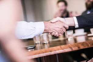 Close up of businesswoman and man shaking hands in board team meetingの写真素材 [FYI03559087]