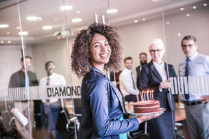 Portrait of young businesswoman carrying celebration cake into boardroomの写真素材 [FYI03559088]