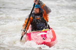 Male kayaker paddling River Dee rapidsの写真素材 [FYI03559187]