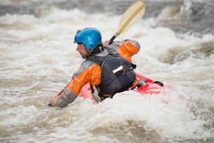 Rear view of male kayaker paddling River Dee rapidsの写真素材 [FYI03559188]
