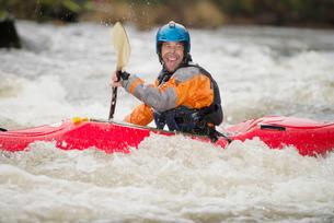 Happy male kayaker paddling River Dee rapidsの写真素材 [FYI03559193]