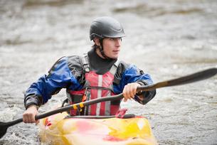 Young male kayaker paddling River Dee rapidsの写真素材 [FYI03559194]