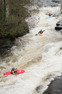 High angle view of kayakers paddling River Dee white water rapids, Llangollen, North Walesの写真素材 [FYI03559203]