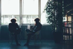 Silhouetted male hipster twins working on laptop and digital tablet in officeの写真素材 [FYI03559231]