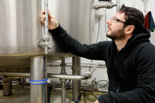 Worker in brewery, checking pressure gauge on brew tankの写真素材 [FYI03559340]