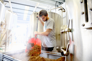 Worker in brewery, emptying grains from mash tunの写真素材 [FYI03559348]
