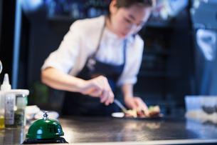 Chef in commercial kitchen preparing foodの写真素材 [FYI03559426]