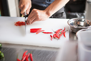 Cropped view of man slicing red chilli peppersの写真素材 [FYI03559430]
