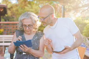 Couple outdoors using smartphonesの写真素材 [FYI03559479]