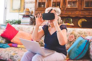 Woman on sofa using virtual reality headsetの写真素材 [FYI03559482]