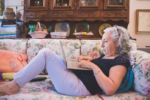 Woman lying on sofa using laptopの写真素材 [FYI03559483]