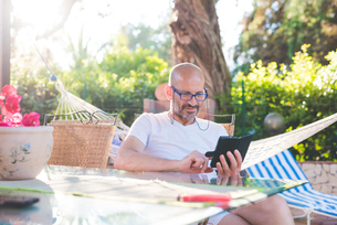 Man sitting outdoors at table using smartphoneの写真素材 [FYI03559484]