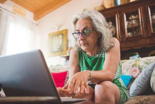Woman on sofa using laptopの写真素材 [FYI03559488]