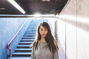 Portrait of young woman standing in underpassの写真素材 [FYI03559660]