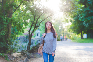Young woman strolling in parkの写真素材 [FYI03559665]