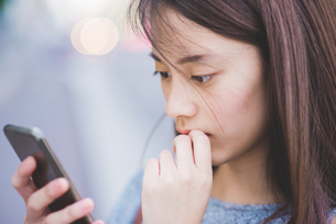 Close up of young woman reading smartphoneの写真素材 [FYI03559673]