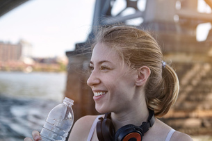 Young woman beside river, wearing headphones around neck, holding water bottle, New York City, USAの写真素材 [FYI03559683]