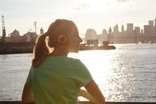 Woman wearing headphones by water, Manhattan, New York, USAの写真素材 [FYI03559706]