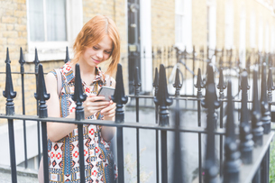 Woman by house texting on smartphone, London, UKの写真素材 [FYI03559718]
