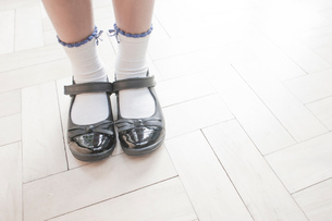 Cropped shot of schoolgirl wearing shoes and ankle socks standing on parquet floorの写真素材 [FYI03559799]