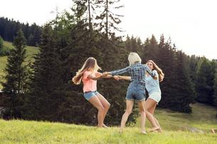 Three female adult friends playing ring-a-rosie in field, Sattelbergalm, Tirol, Austriaの写真素材 [FYI03559800]