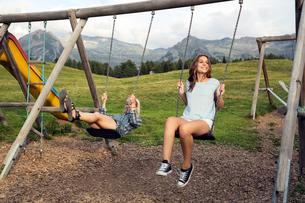 Two female adult friends playing on swings in Austrian Alps, Sattelbergalm, Tirol, Austriaの写真素材 [FYI03559828]