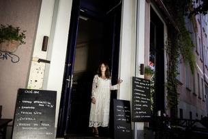Woman in cafe doorway looking away, Berlin, Germanyの写真素材 [FYI03559951]