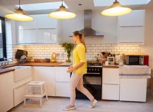 Mid adult woman walking in stylish kitchenの写真素材 [FYI03560024]
