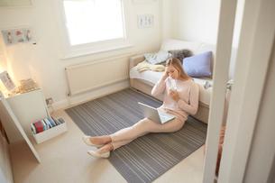 Mid adult woman sitting on living room floor using laptopの写真素材 [FYI03560035]
