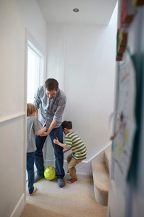 Mid adult man playing soccer with sons in hallwayの写真素材 [FYI03560045]