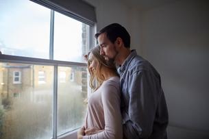 Mid adult couple gazing out through bedroom windowの写真素材 [FYI03560057]