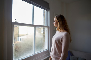 Mid adult woman gazing out through bedroom windowの写真素材 [FYI03560058]