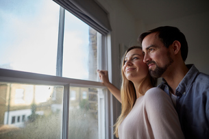 Mid adult couple looking out through bedroom windowの写真素材 [FYI03560060]