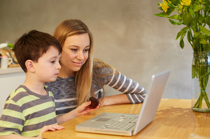 Mid adult woman and son looking at laptop on dining tableの写真素材 [FYI03560073]
