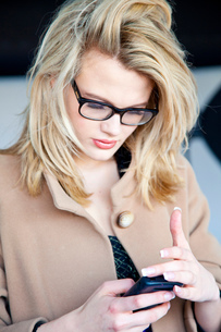 Blond young woman wearing eye glasses reading  smartphone textsの写真素材 [FYI03560135]