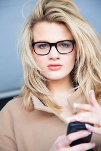 Portrait of blond young woman wearing eye glasses holding smartphoneの写真素材 [FYI03560137]