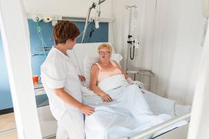 Nurse tending to patient in hospital bedの写真素材 [FYI03560179]