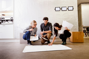Architects in office discussing blueprintsの写真素材 [FYI03560254]